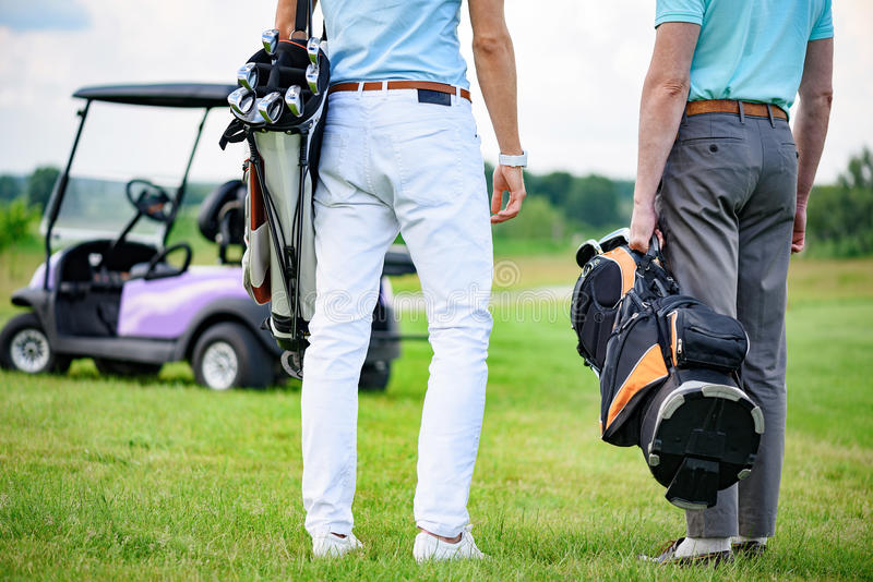 Two partners of game standing on golf course royalty free stock image