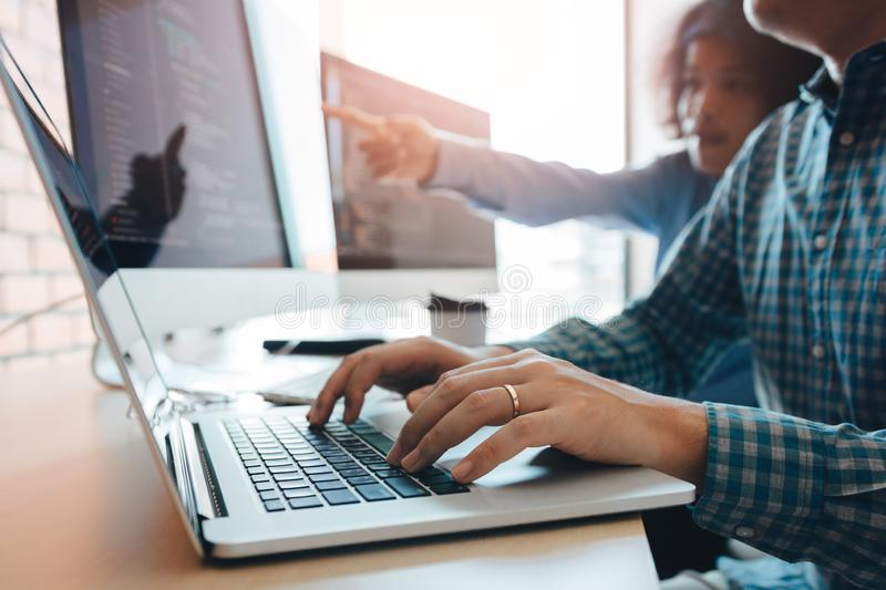 Two partnerships developing programming and coding technologies working on laptop and analyzing together stock image
