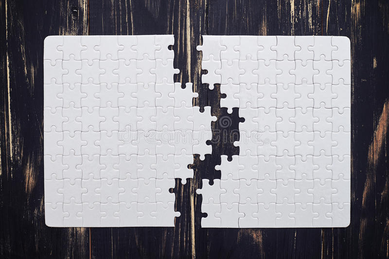 Download Two Parts Of A Puzzle On Dark Wooden Desk Stock Illustration - Illustration: 70384699
