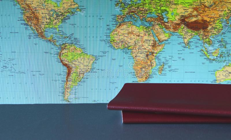Two passports lie on the background of the world map, the concept of travel and the choice of route for the trip stock photos
