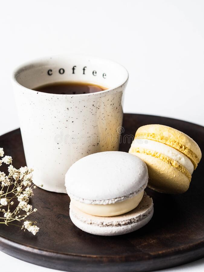 Two pastel macaroons with white ceramic cup of black coffee on wood plate on white background. Two pastel macaroons with white ceramic cup of black coffee on stock photo