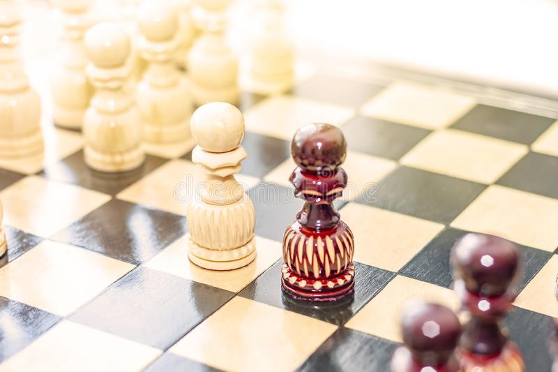 Two pawns, black and white on the chessboard. stock images