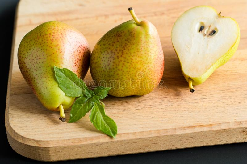 Two pears and piece of a pear with fresh basil leaves on a wooden cutting board, side view stock images