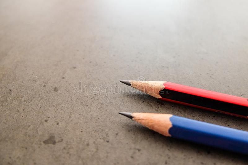 Two pencils on a dark gray table stock photos