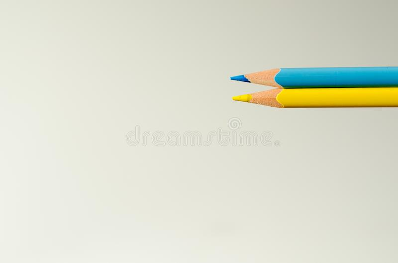 Two pencils of yellow and blue colour on white sheet background. stock photo