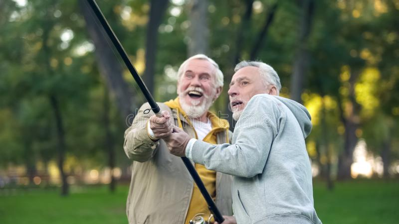 Two pensioners catching big fish, pulling spinning together, friendship support royalty free stock photo