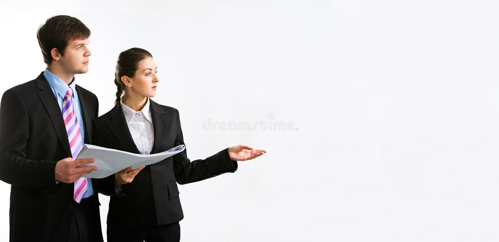 Two people. Image of two business people holding a document and looking at something