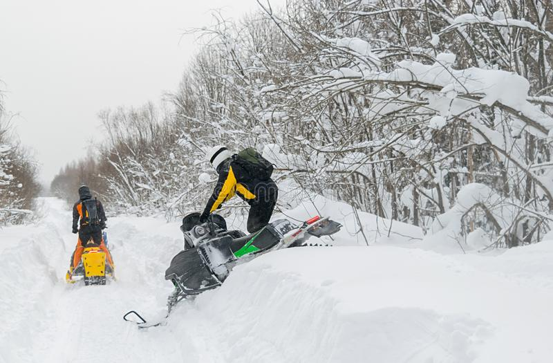 Two people, athletes, ride on snowmobiles on a snow-covered road stock image