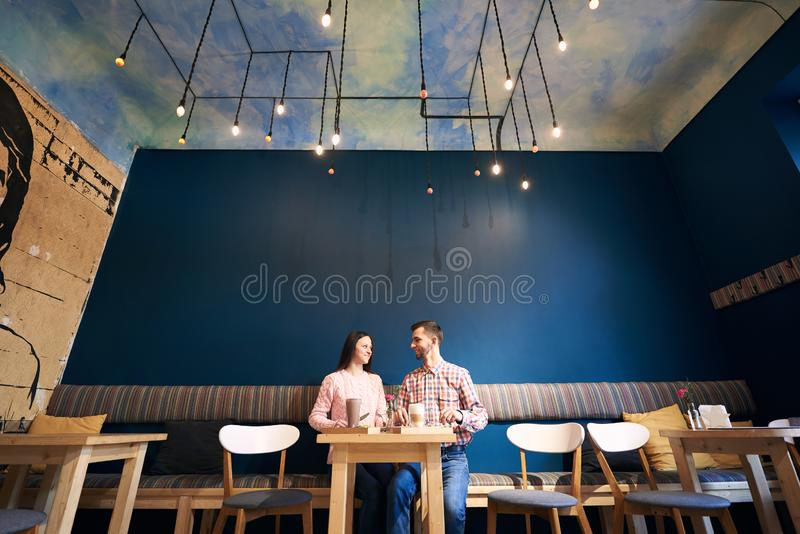Two people in atmospheric cafe enjoying time spending with each other, having dinner, talking in cafe. Blue background. royalty free stock images