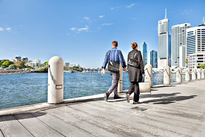 Two people with the business suit walking on riverside street stock photos