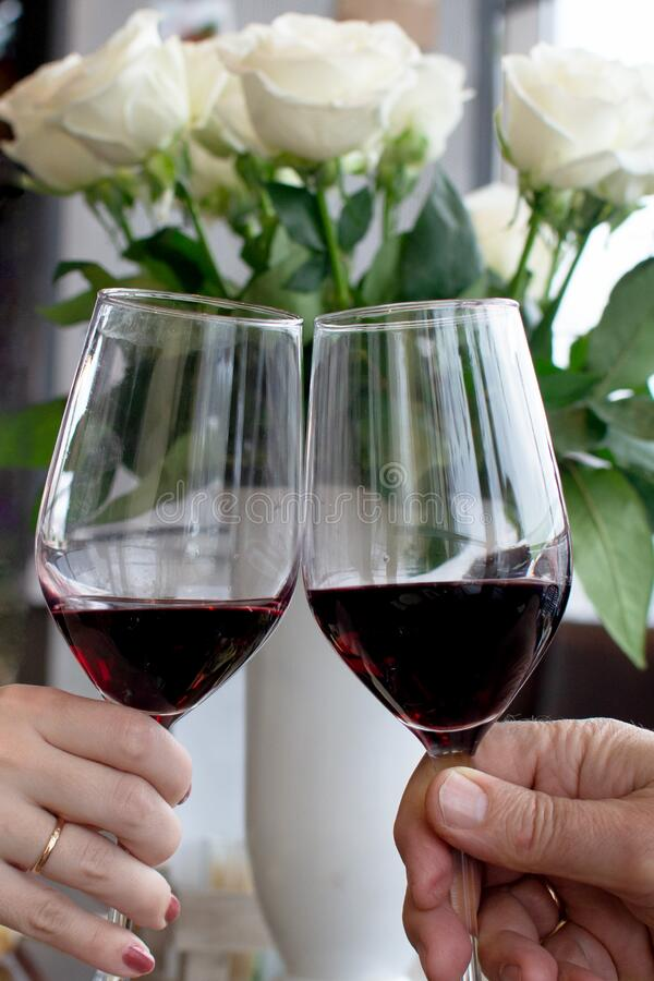 Two people clinking each other's glasses with red wine. Hand of young woman and old man stock photography