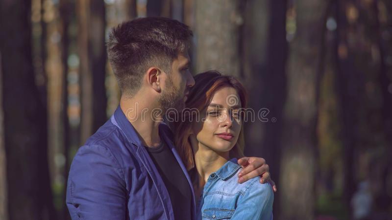 Two people on a date in town. Caucasian cute family.Man and women talking in the park in the early morning. Happy pair hug and speak on a date. Couple in love royalty free stock image