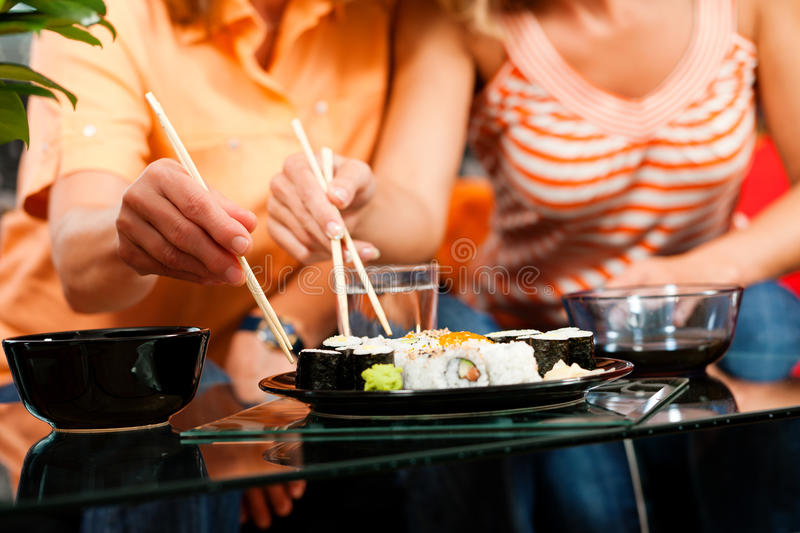 Two people eating sushi stock images