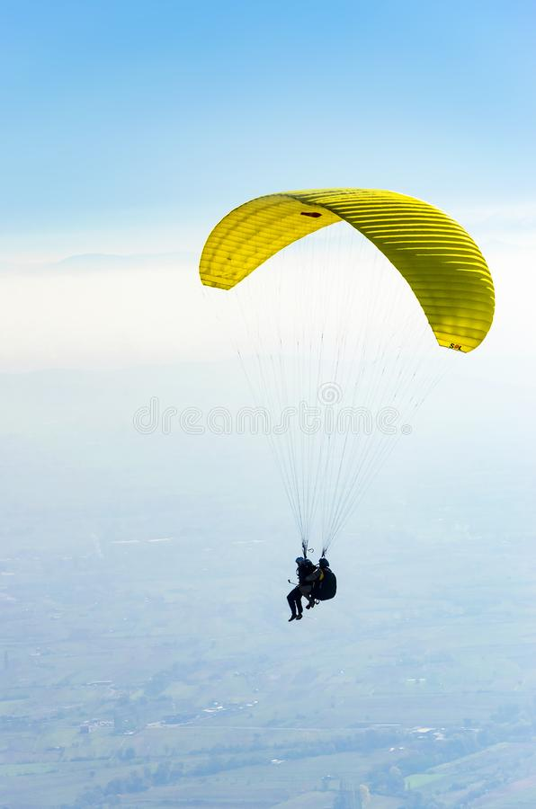 Two people are flying in tandem on a paraglider stock photo