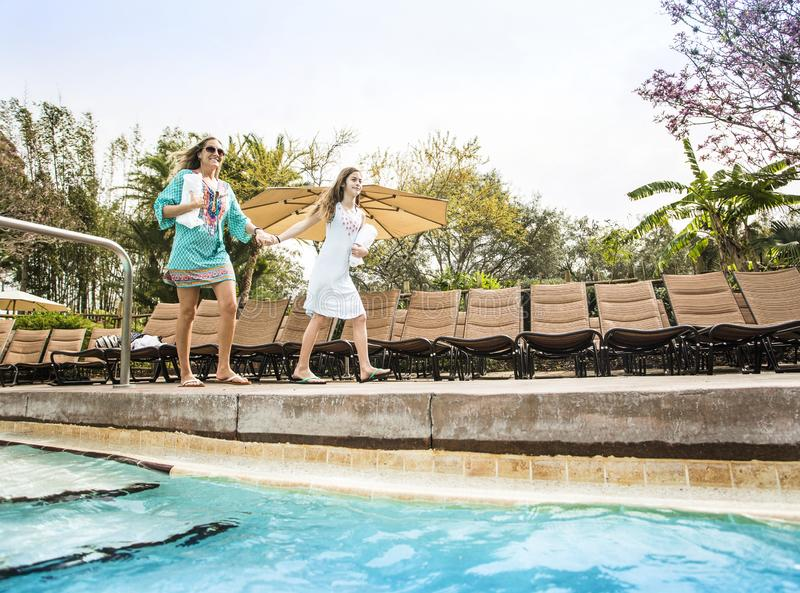 Two people going swimming in a large outdoor resort pool. Low angle view of two people entering in a luxurious outdoor swimming pool at a beautiful resort stock image