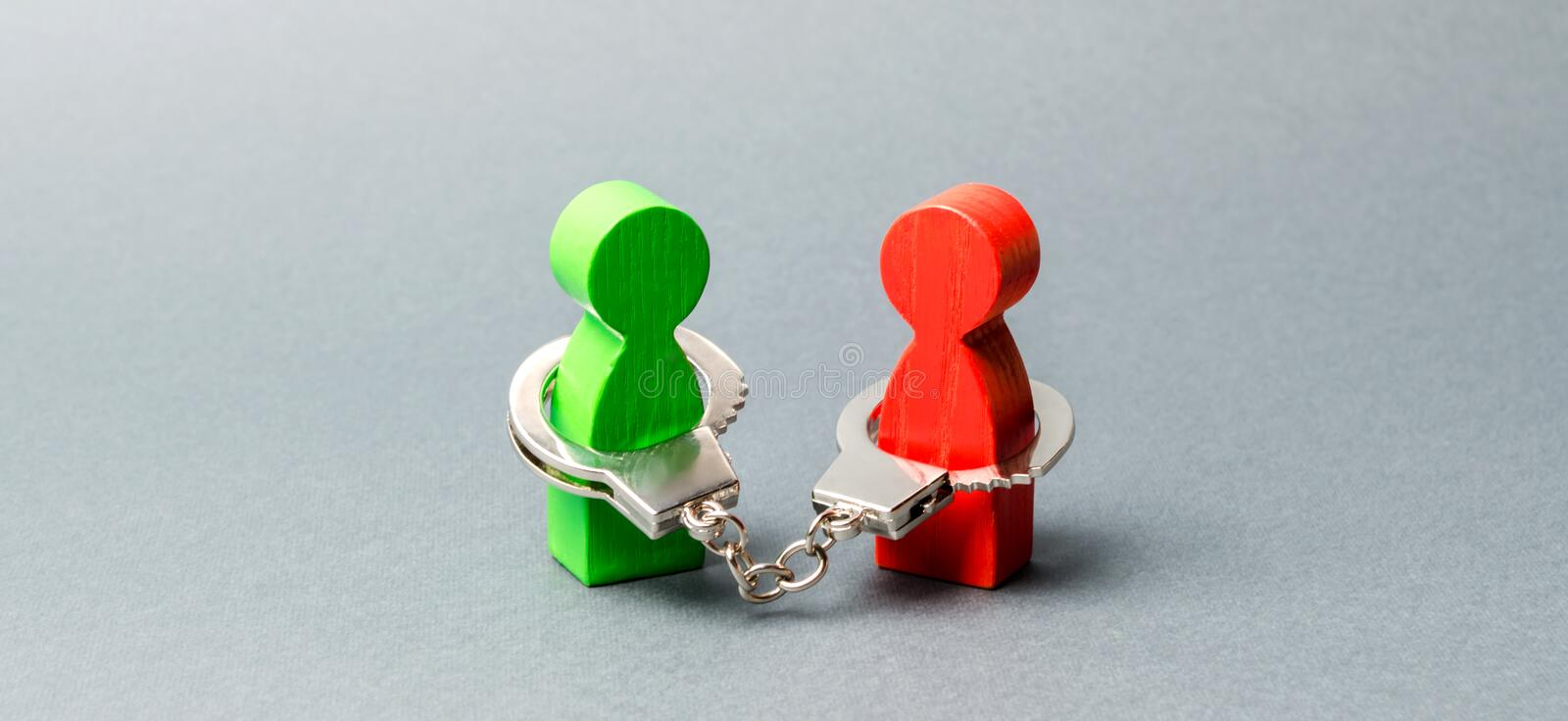 Two people are handcuffed. Unbreakable bond. Strong trusting relationships and reliable partners. Business deal concept. Transaction. Support. Wooden figures stock images