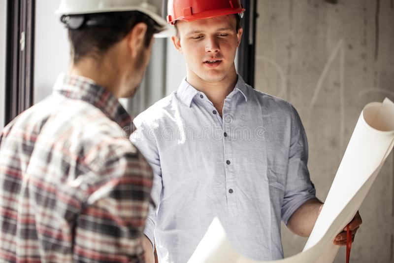 Two people having a degree of engineering with blueprint stock images