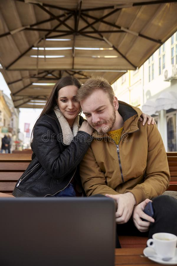 Two people hugging couple, looking at a laptop computer in a cafe royalty free stock images
