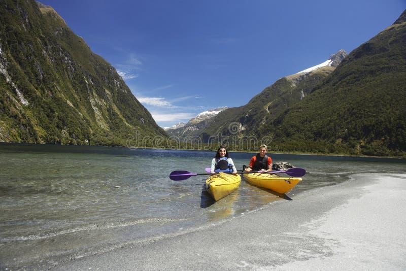 Two People Kayaking In Mountain Lake stock photo