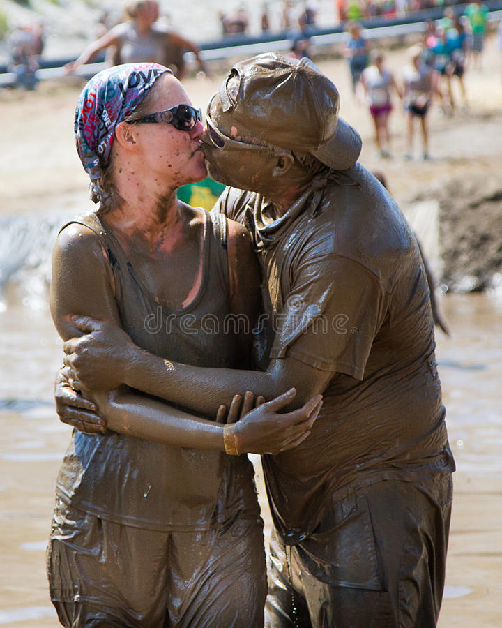 Two people kiss during the mud race royalty free stock photo