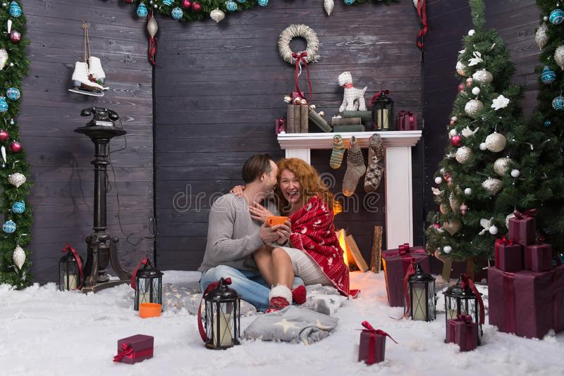 Two people laughing while hugging in New Year decorated room. Cheerful relaxed young women hugging her husband and laughing while sitting on fluffy carpet near stock images