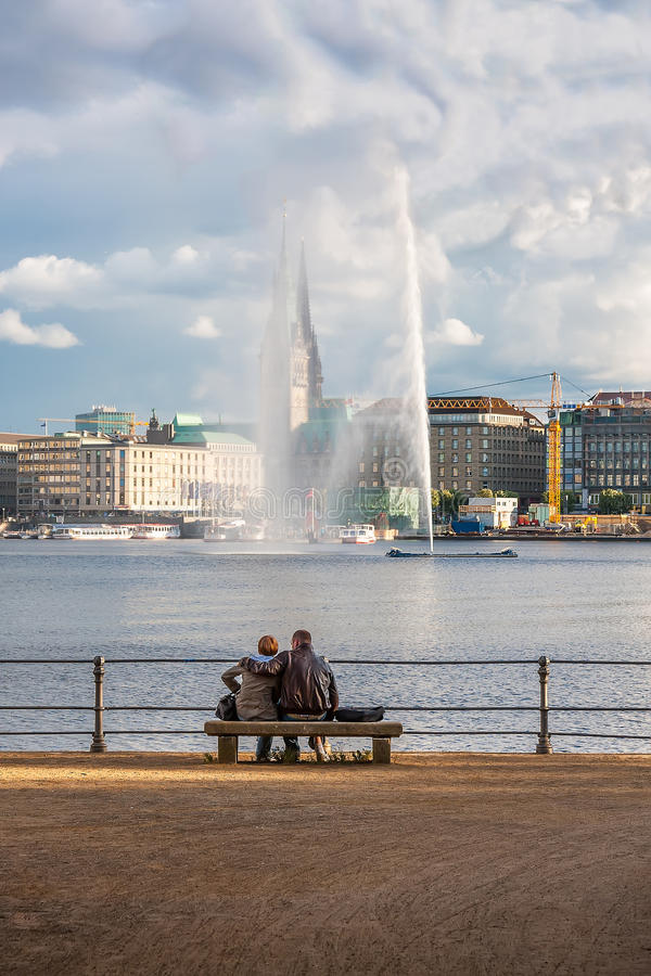 Two people look at the fountain in the center of Hamburg. royalty free stock photos