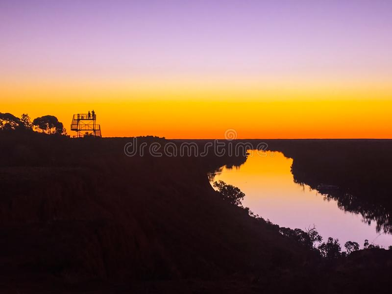 Two people on lookout platform overlooking river. Silhouettes of two people on lookout platform overlooking river at beautiful sunset royalty free stock images