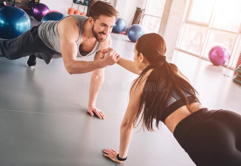 Two people that love fitness are standing on one hand in plank position and holding each other with another hand with a stock images