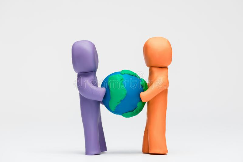 Two people made from plasticine holding a model of planet earth away from one another stock photography