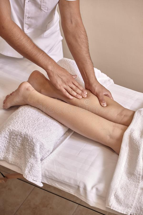 Two people, man physiotherapist leg massage, close up royalty free stock photography
