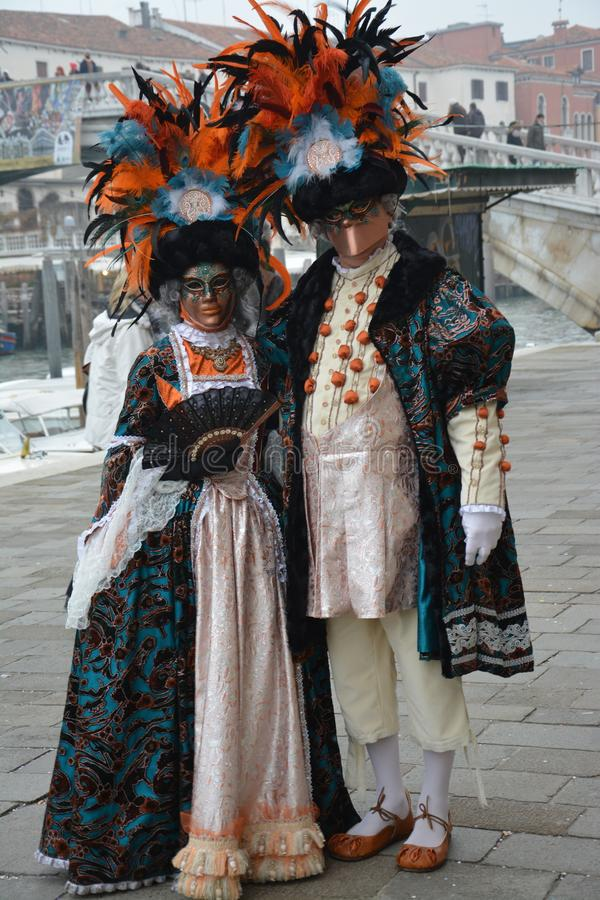 Two people masked during the carnival in Venice pose for the photo near a canal. Two people, a man and a woman, masked during the carnival in Venice pose for the stock photography