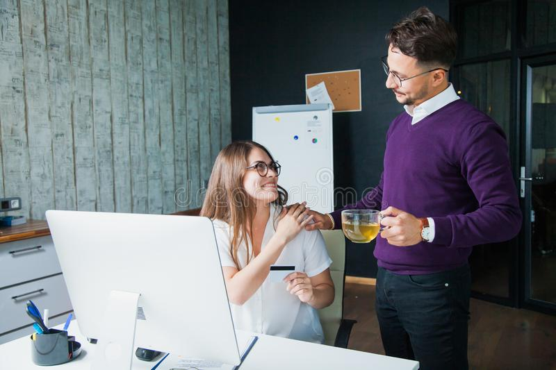 Two people man and woman at office with computer screen and credit card stock photography