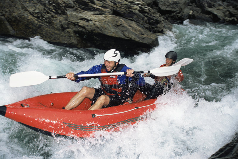 Two people paddling inflatable boat down rapids stock photos