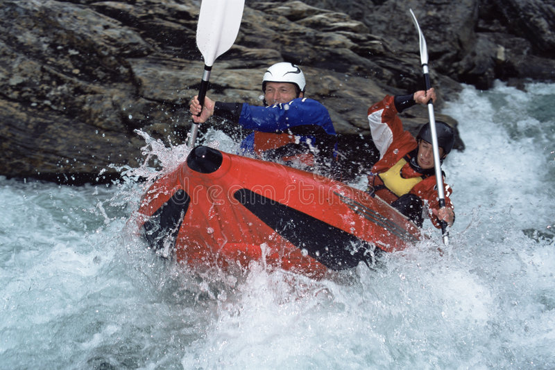 Two people paddling inflatable boat down rapids stock image