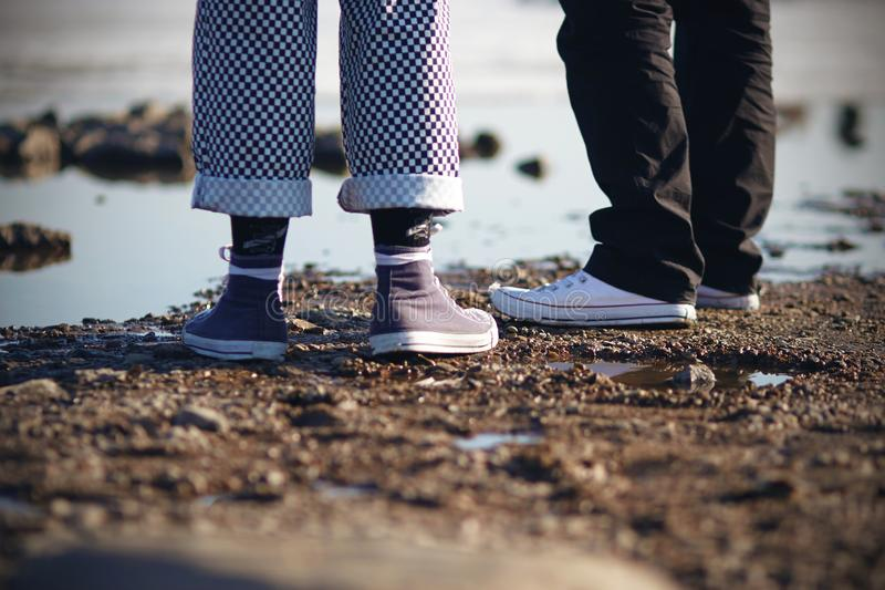 Two people in sneakers are on the beach stock image