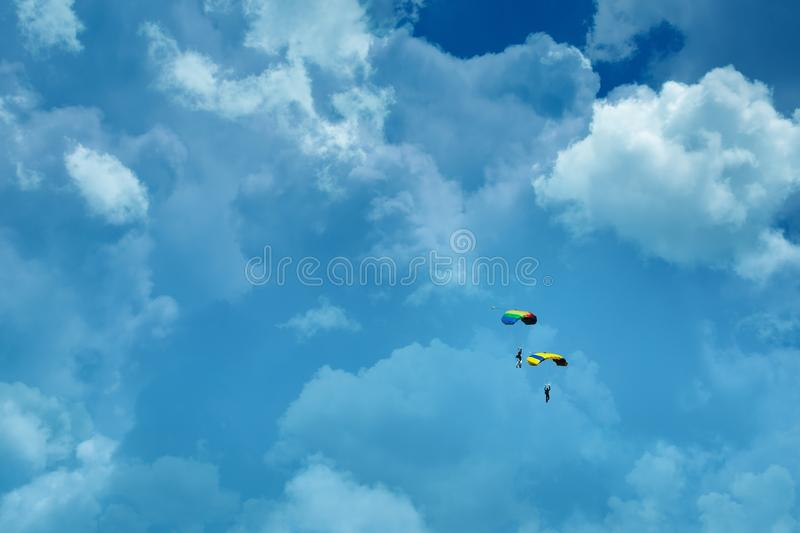 People parachuting and sky. Two people parachuting in cloudy sky stock photo