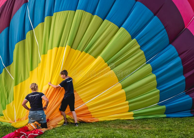 Two people pick up the balloon stock images