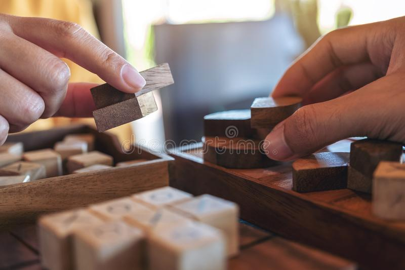 Two people playing and building round wooden puzzle game. Closeup image of two people playing and building round wooden puzzle game stock images