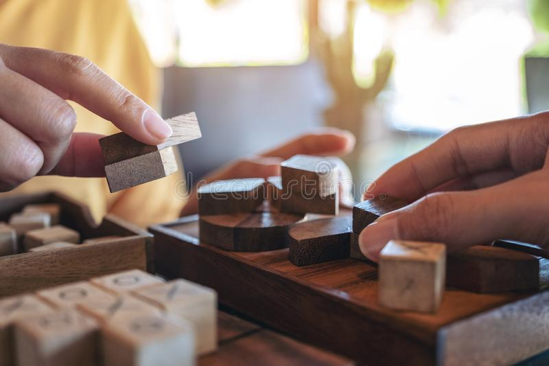 Two people playing and building round wooden puzzle game. Closeup image of two people playing and building round wooden puzzle game stock photo