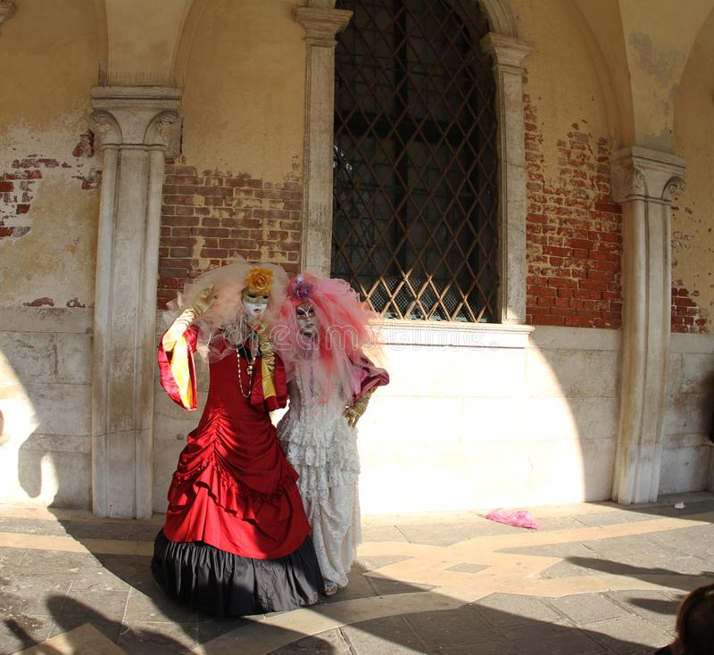 Two people posing in costumes Venice Carnival 2019. Red and white dress royalty free stock images