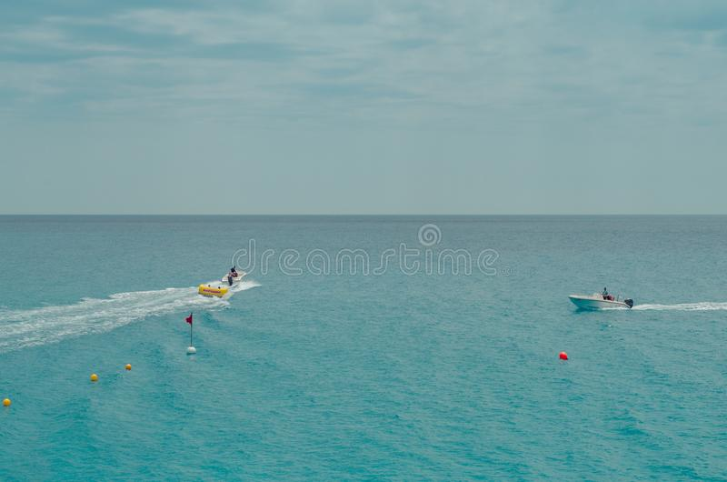 Two People Rides Watercrafts On Body Of Water Under Clear Blue Sky stock photography