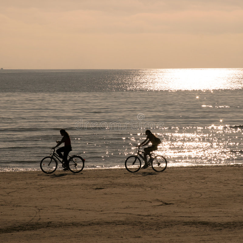 Two people riding bicycles stock photo