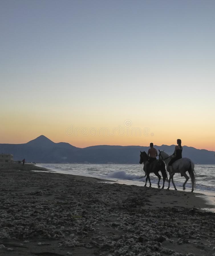 Two horse riders in the beach at dusk royalty free stock images