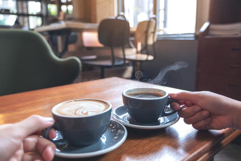 Two people`s hands holding coffee and hot chocolate cups on wooden table in cafe. Closeup image of two people`s hands holding coffee and hot chocolate cups on royalty free stock photography