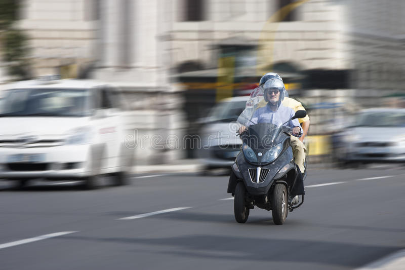 Two people on a scooter beverly three-wheel scooter (panning effect). Two people on a scooter in the historic center of Rome (Italy) on the Ponte Vittorio royalty free stock image