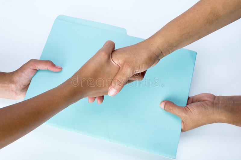 Two people shaking hands and exchanging documents as a sign of agreement. Blue folder and documents royalty free stock photography
