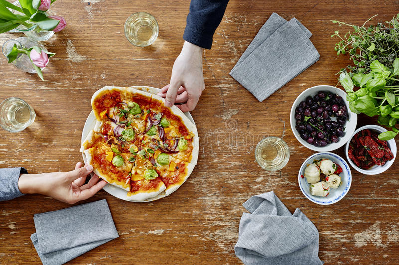 Two people sharing freshly made vegetarian pizza royalty free stock images