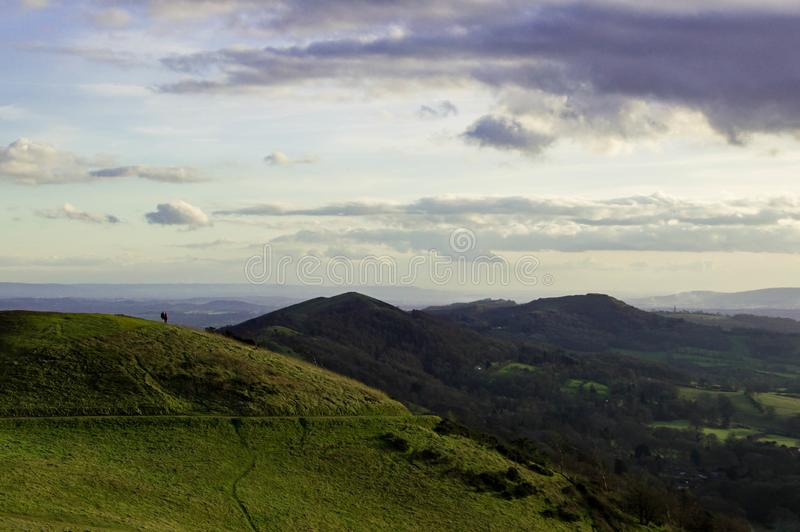 Two people silhouetted in the distance looking from the top of a hill on a sunny winters days. Malvern Hills, England stock images