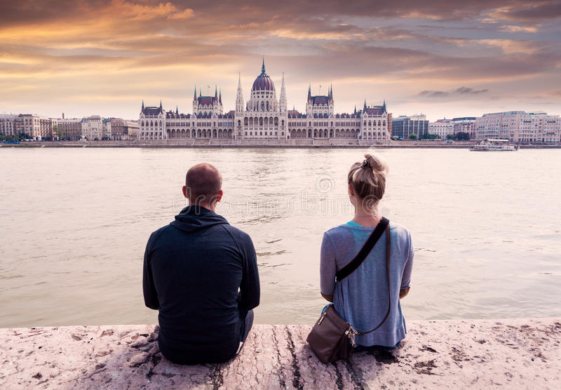 Two people sit on the waterfront and enjoy the view of the parliament in Budapest, Hungary. A couple in love sits on the embankment and enjoys the view of royalty free stock photo