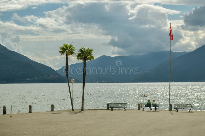 Two people sitting on the bench on Lago Maggiore shore in Ascona, Switzerland. Ascona, Switzerland - September 2, 2018: Two people sitting on the bench on Lago stock photos